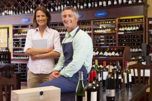 Smiling business owners with digital tablet in wine shop